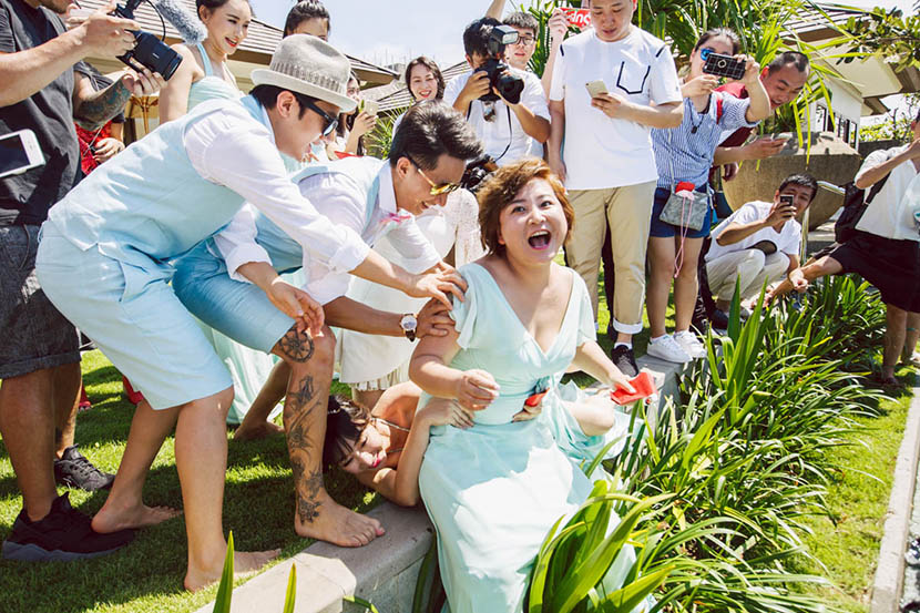 Liu Yan, lying on the ground, holds onto Jia Ling, also a bridesmaid, to avoid being thrown into a swimming pool during Bao Beier's wedding in Bali, Indonesia, March 30, 2016.  VCG