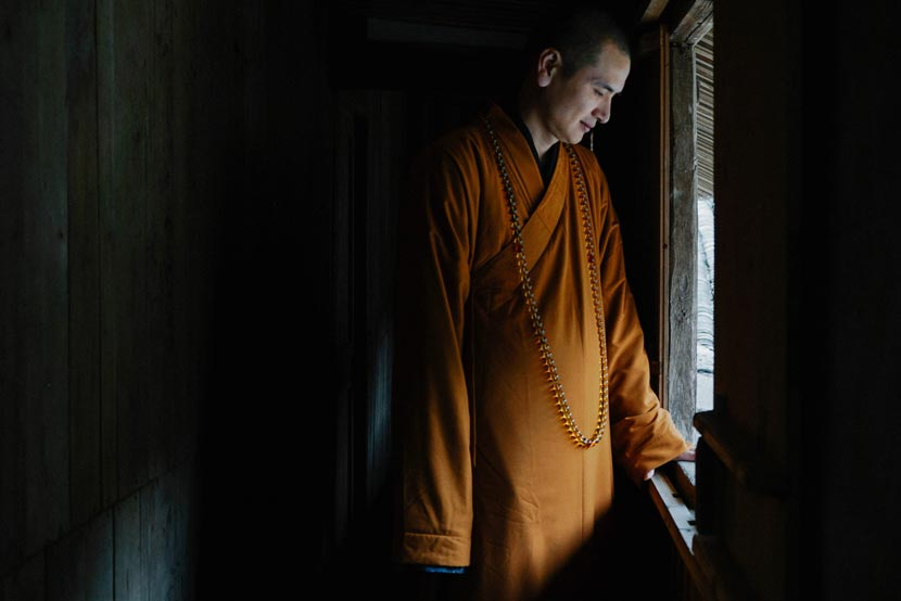 Shi Mingxing stands next to a window at Pu'an Temple, Wenzhou, Zhejiang province, Feb. 21, 2017. Wu Yue/Sixth Tone