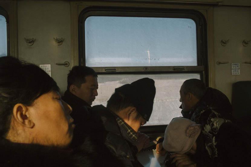 A commuter train carrying miners travels past wind turbines in Shuangyashan, Heilongjiang province, Jan. 11,2016.  Zhou Pinglang/VCG