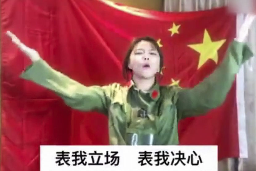 Mu Yalan stands in front of a Chinese flag and raises her hands in a screenshot from an anti-Lotte video posted on March 13, 2017.