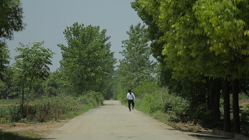 A still frame from 'Still Tomorrow' shows Yu Xiuhua walking along a country road. Courtesy of Fan Jian