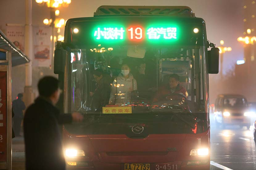 A man waits for a bus in Shijiazhuang, Hebei province, Dec. 19, 2016. The city implements an even-odd license plate plan to limit vehicles on the road and offers free bus service to citizens during heavy air pollution days. Xie Kuangshi/Sixth Tone