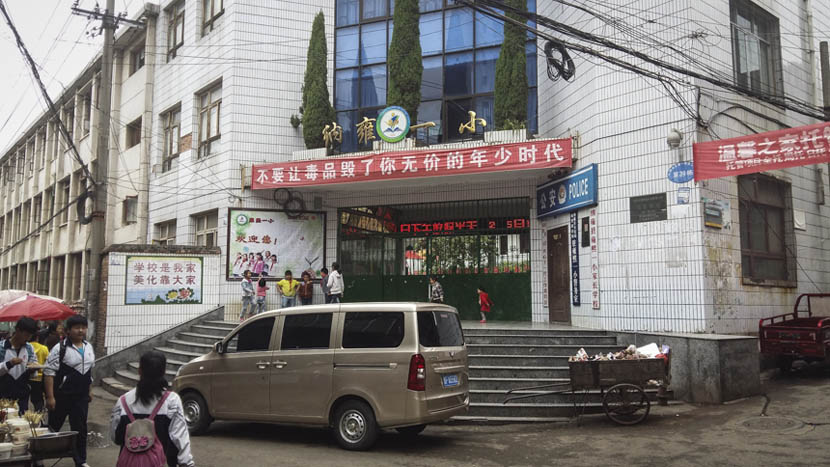 """A banner hanging above the entrance of Nayong No. 1 Primary School in Guizhou province says, """"Don't let drugs ruin your priceless childhood,"""" May 6, 2015.  Duan Yanchao/Sixth Tone"""